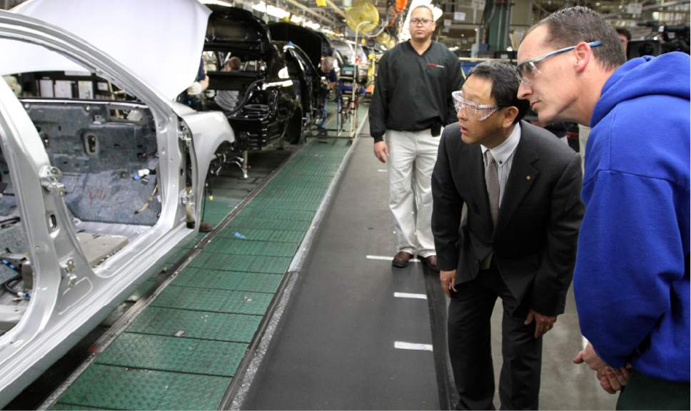 FILE - In this Thursday, Feb. 25, 2010, file photo, production team member Steve Turley, right, and Toyota President Akio Toyoda look into a Camry on the assembly line at the Toyota Motor Manufacturing plant in Georgetown, Ky. Toyota said Monday, April 10, 2017, it is investing $1.3 billion to retool its sprawling Georgetown factory, where the company's flagship Camry sedans are built. No new factory jobs are being added, but Toyota says the upgrades amount to the biggest single investment ever at one of its existing plants in the United States. (AP Photo/James Crisp, File)