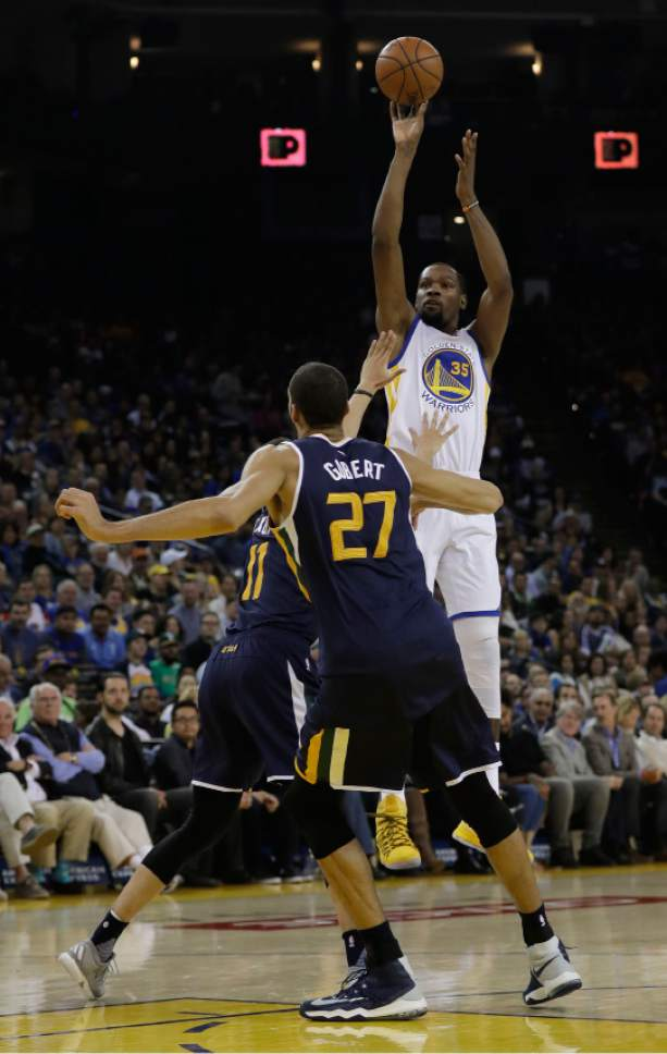 Golden State Warriors forward Kevin Durant (35) shoots over Utah Jazz center Rudy Gobert (27) during the first half of an NBA basketball game, Monday, April 10, 2017, in Oakland, Calif. (AP Photo/Marcio Jose Sanchez)