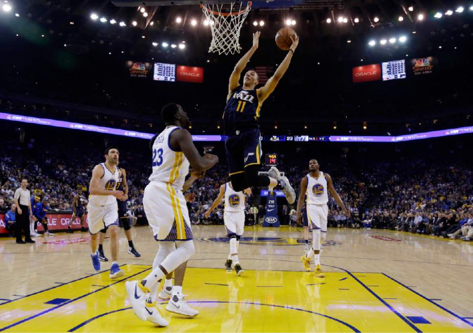 Utah Jazz guard Dante Exum (11) scores over Golden State Warriors forward Draymond Green (23) during the first half of an NBA basketball game, Monday, April 10, 2017, in Oakland, Calif. (AP Photo/Marcio Jose Sanchez)