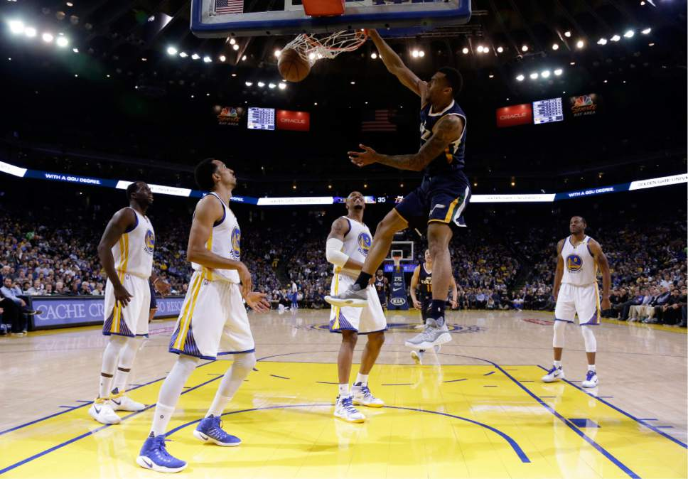 Utah Jazz forward Joel Bolomboy, top, dunks against the Golden State Warriors during the first half of an NBA basketball game, Monday, April 10, 2017, in Oakland, Calif. (AP Photo/Marcio Jose Sanchez)