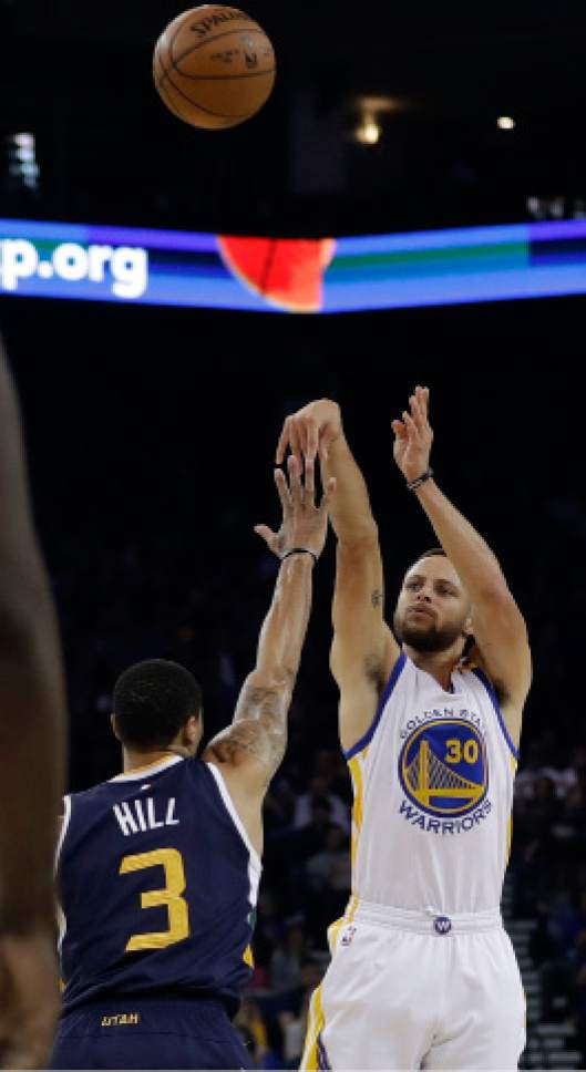 Golden State Warriors guard Stephen Curry (30) shoots over Utah Jazz guard George Hill (3) during the first half of an NBA basketball game, Monday, April 10, 2017, in Oakland, Calif. (AP Photo/Marcio Jose Sanchez)