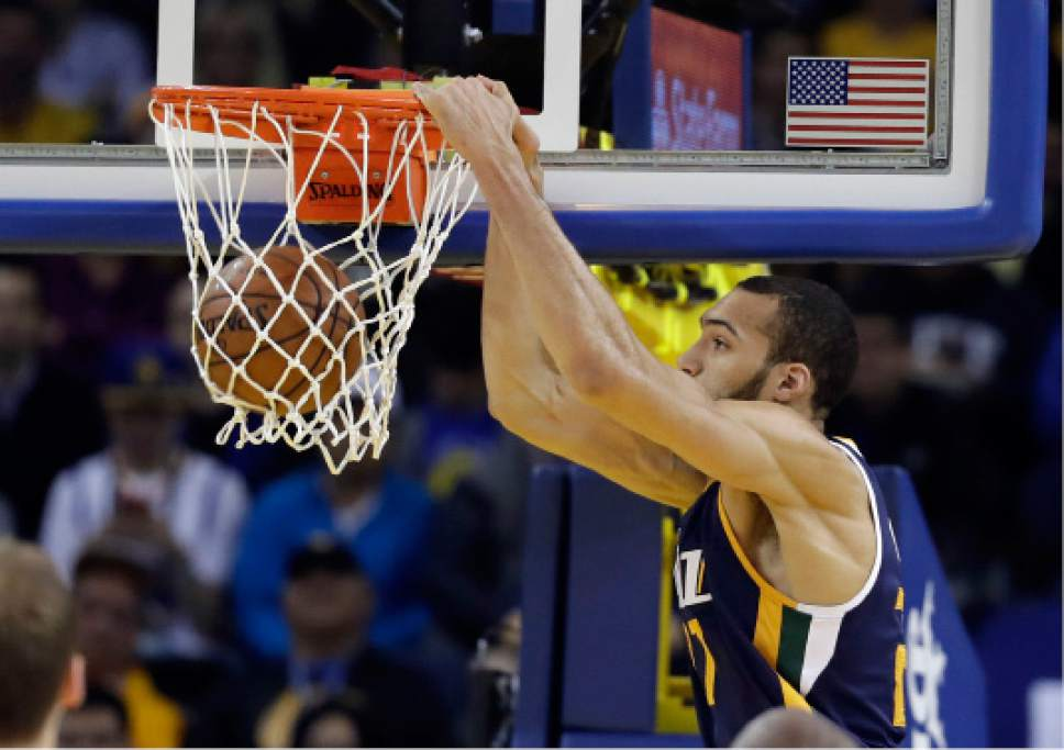 Utah Jazz center Rudy Gobert (27) dunks against the Golden State Warriors during the first half of an NBA basketball game, Monday, April 10, 2017, in Oakland, Calif. (AP Photo/Marcio Jose Sanchez)