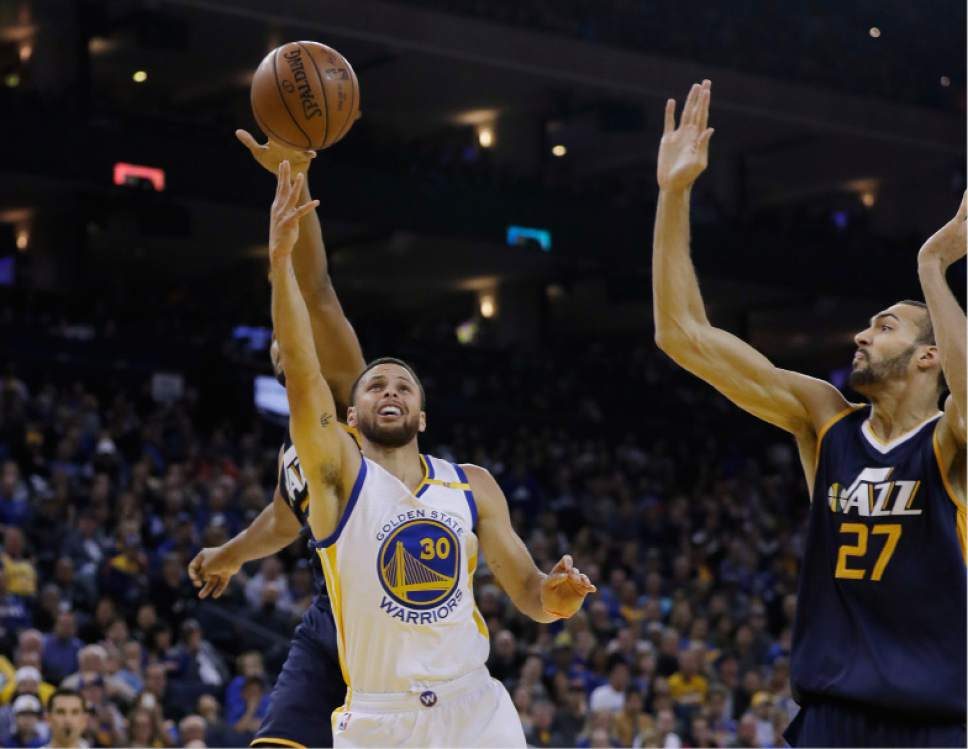 Golden State Warriors guard Stephen Curry (30) shoots next to Utah Jazz center Rudy Gobert (27) during the first half of an NBA basketball game, Monday, April 10, 2017, in Oakland, Calif. (AP Photo/Marcio Jose Sanchez)