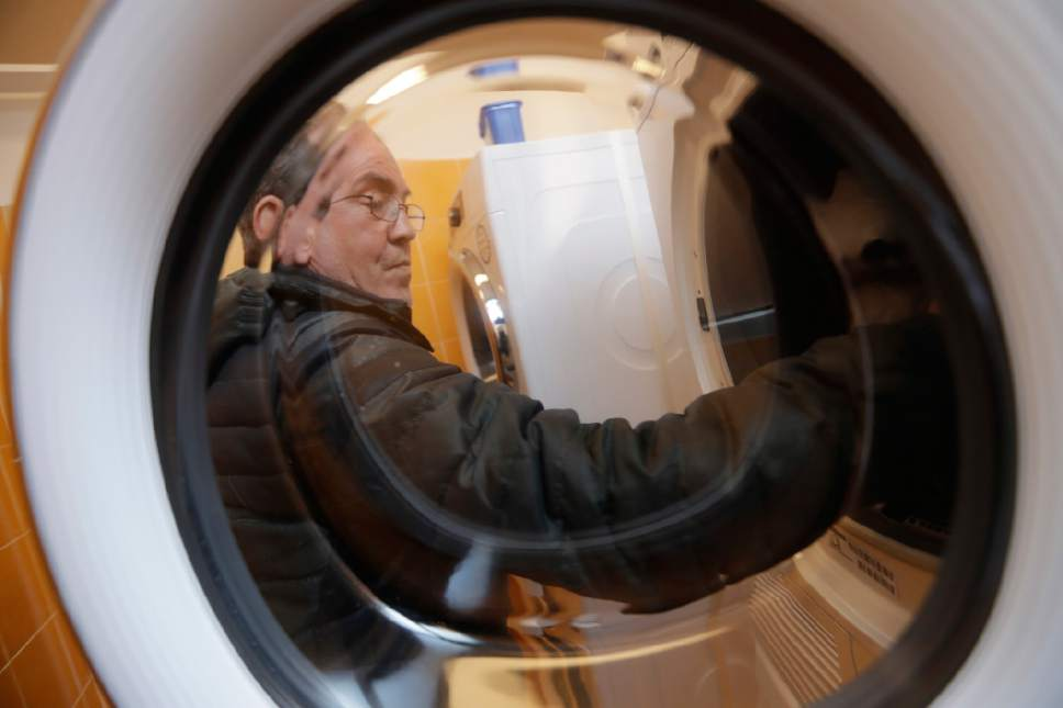 Giuseppe, 53, puts clothes inside a washing machine in a laundry opened in the Sant' Egidio Community Center in Rome, Tuesday, April 11, 2017. Pope Francis has opened a new laundromat for the homeless to wash, dry and iron their clothing and blankets.  The laundromat, not far from the Vatican, has six washing machines, six dryers and several ironing boards and irons. (AP Photo/Alessandra Tarantino)