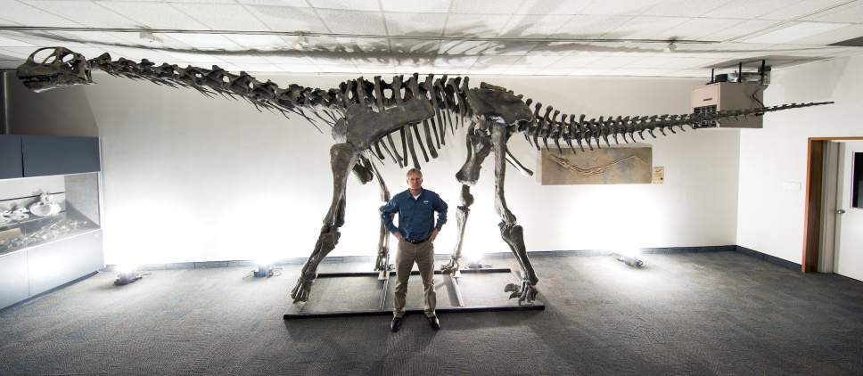 |  Courtesy of Brigham Young University  BYU geology professor Brooks Britt poses with a mount of moabosaurus, a newly characterized species of dinosaur named for Moab. Britt has spent 40 years examining 5,500 bone fragments recovered from Dalton Wells near Arches National Park before publishing his findings this week.
