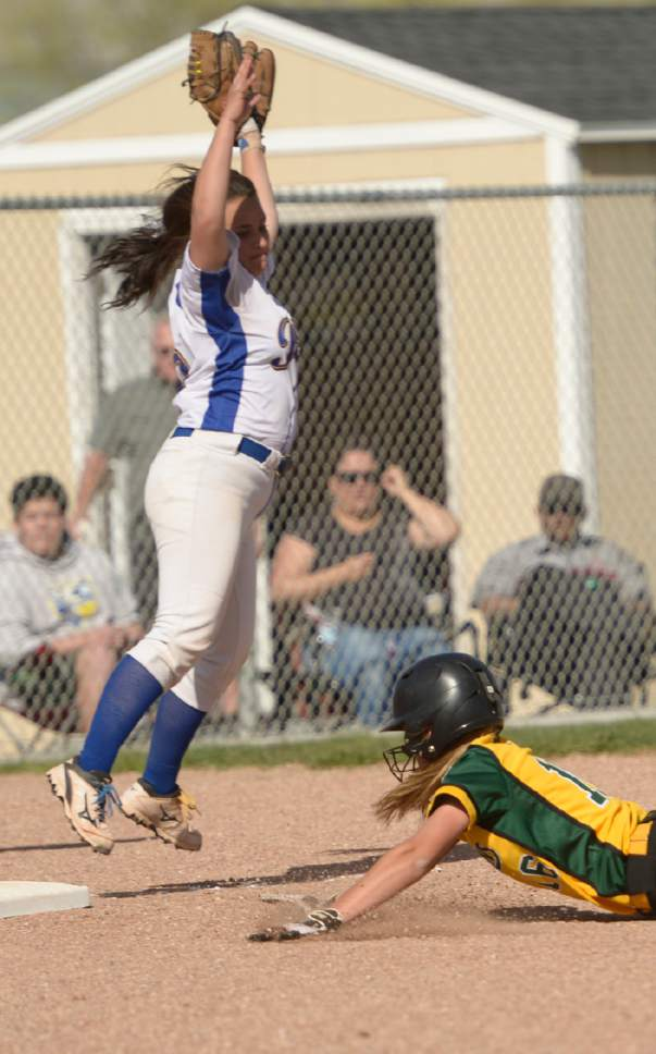 Leah Hogsten  |  The Salt Lake Tribune  Cyprus' Lexi Tahoni can't make the out on Kearns' Shyann Beddow who slides safely into third. Cyprus High School girls' softball team defeated Kearns High School 5-0 during their game Thursday, April 13, 2017 in Magna.