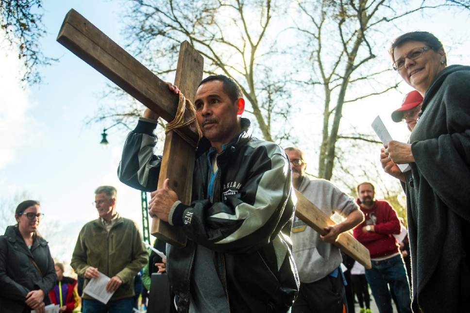 "Chris Detrick  |  The Salt Lake Tribune John Salazar, front, and Alex Bury carry the cross from the  Cathedral of the Madeline during the annual Good Friday Procession of the Cross Saturday, April 15, 2017.  Since 1983, the Salt Lake Council of Churches has sponsored this annual procession, which is similar to the tradition of the ""Via Dolorosa"" (Way of Suffering), where pilgrims to Jerusalem follow the path Jesus took to the cross."