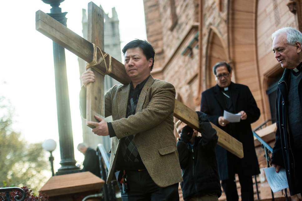 "Chris Detrick  |  The Salt Lake Tribune Vichen Lee, of Salt Lake City, carrie the cross from First Presbyterian Church during the annual Good Friday Procession of the Cross Saturday, April 15, 2017.  Since 1983, the Salt Lake Council of Churches has sponsored this annual procession, which is similar to the tradition of the ""Via Dolorosa"" (Way of Suffering), where pilgrims to Jerusalem follow the path Jesus took to the cross."