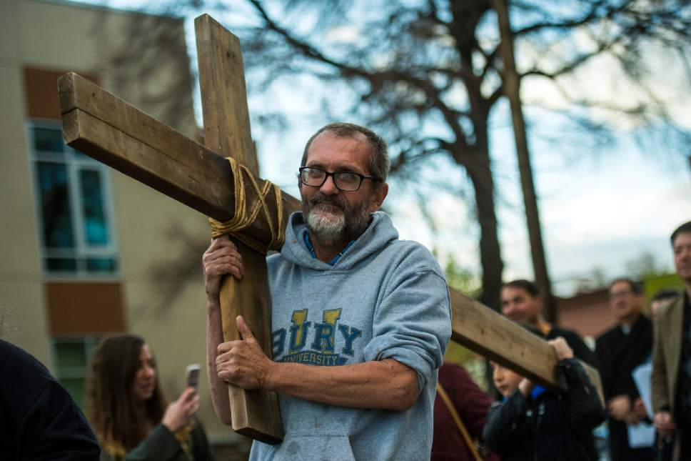 "Chris Detrick  |  The Salt Lake Tribune Alex Bury carries the cross down 400 East to the Crossroads Urban Center during the annual Good Friday Procession of the Cross Saturday, April 15, 2017.  Since 1983, the Salt Lake Council of Churches has sponsored this annual procession, which is similar to the tradition of the ""Via Dolorosa"" (Way of Suffering), where pilgrims to Jerusalem follow the path Jesus took to the cross."