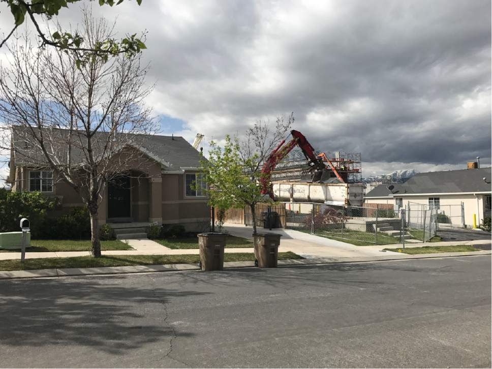 Josh Aune  |  Courtesy   Neighbors watch as a home owned by Draper's American Preparatory Academy is demolished Friday morning to make way for an emergency access route to the construction site of a new charter high school.