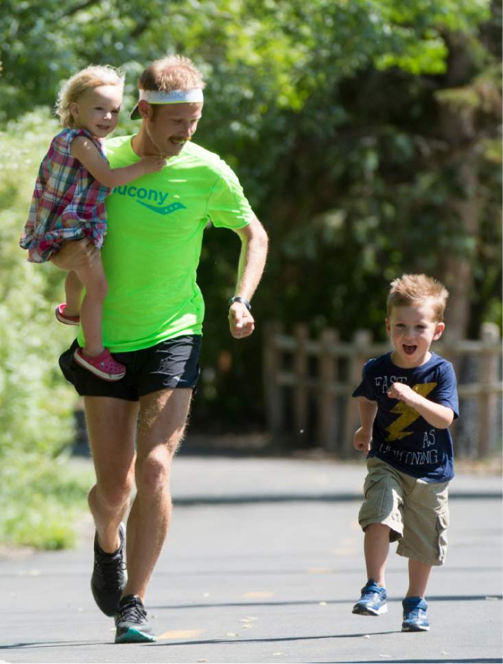 Rick Egan  |  The Salt Lake Tribune  Former BYU distance runner Jared Ward, holds his 2-year-old Ellie, as he races his 4-year-old son Paul, on the Rail Trail in Park City, Tuesday, June 21, 2016.