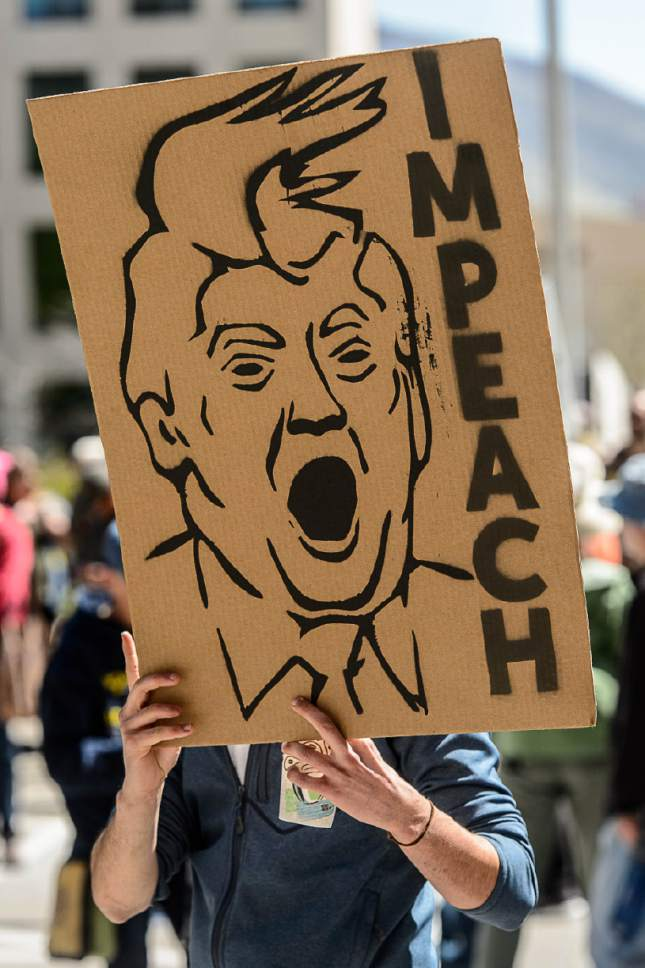 Trent Nelson  |  The Salt Lake Tribune A protestor holds a sign calling for impeachment during a rally calling for President Trump to release his tax returns, which took place at the Salt Lake City and County Building, Saturday April 15, 2017.