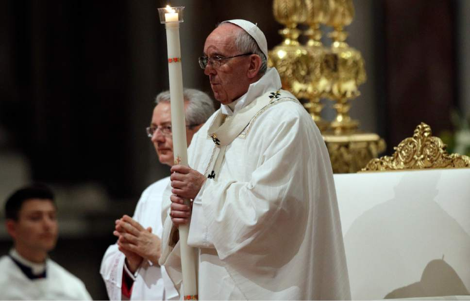 Pope Francis holds a candle as he presides over a solemn Easter vigil ceremony in St. Peter's Basilica at the Vatican, Saturday, April 15, 2017. (AP Photo/Andrew Medichini)
