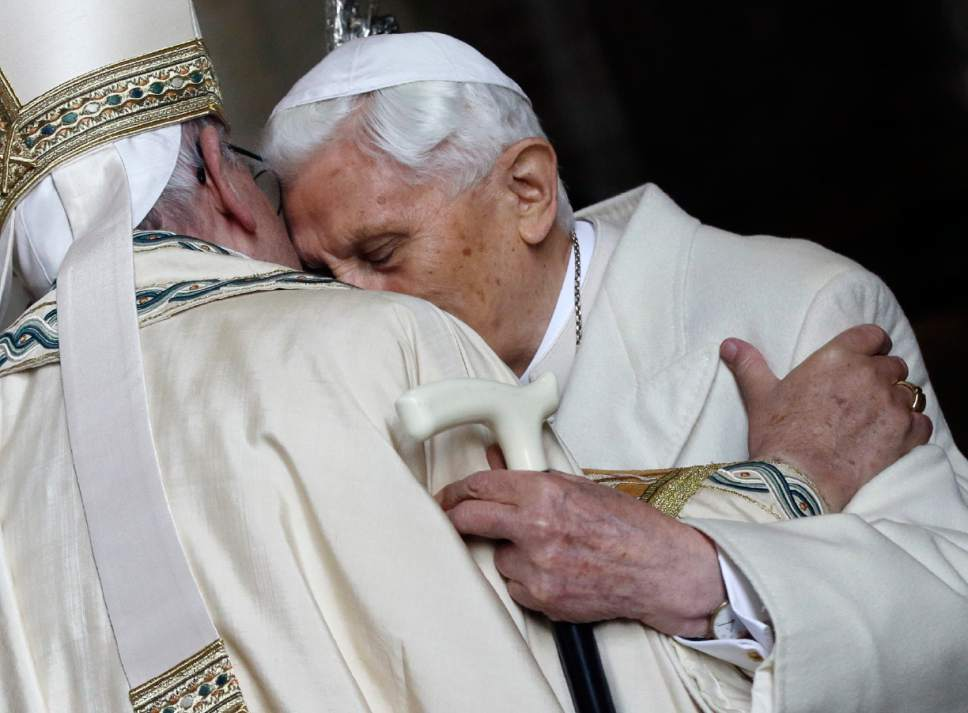 """FILE - In this Tuesday, Dec. 8, 2015 file photo, Pope Emeritus Benedict XVI, right, hugs Pope Francis in St. Peter's Basilica during the ceremony marking the start of the Holy Year, at the Vatican. A """"modest"""" 90th birthday party is being planned for Benedict XVI, who stunned the Catholic church by resigning in 2013. His aide, Monsignor Georg Gaenswein, says Benedict's birthday, which falls on Easter Sunday this year, will be celebrated on Monday in Bavarian style in keeping with the emeritus pontiff's roots. (AP Photo/Gregorio Borgia, File)"""
