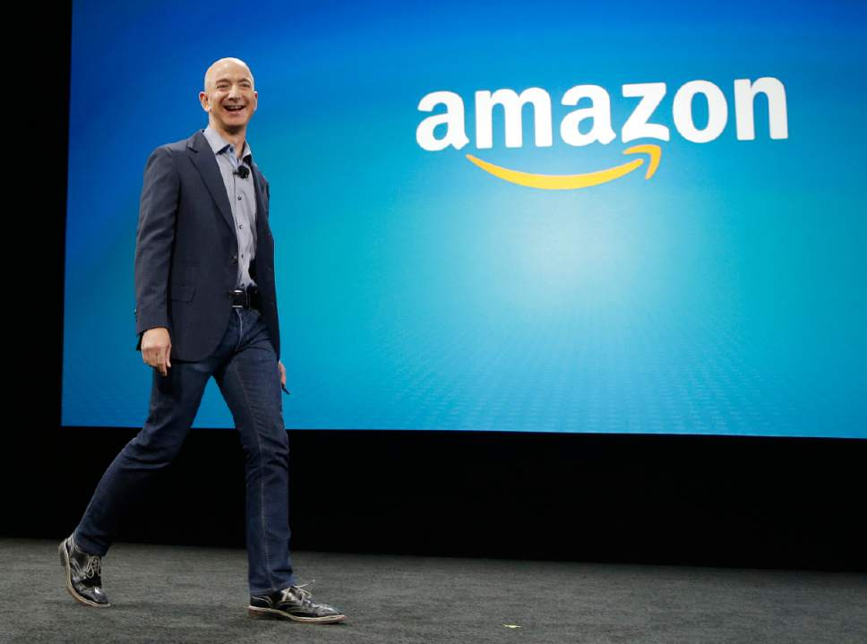 FILE - In this June 18, 2014 file photo, Amazon CEO Jeff Bezos walks on stage for the launch of the new Amazon Fire Phone, in Seattle. Amazon launched on the web twenty years ago on July 16, 1995. (AP Photo/Ted S. Warren, File)