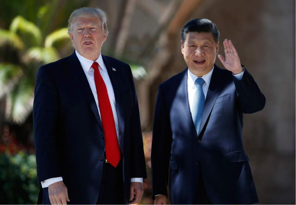 President Donald Trump and Chinese President Xi Jinping pause for photographs at Mar-a-Lago, Friday, April 7, 2017, in Palm Beach, Fla. Trump was meeting again with his Chinese counterpart Friday, with U.S. missile strikes on Syria adding weight to his threat to act unilaterally against the nuclear weapons program of China's ally, North Korea. (AP Photo/Alex Brandon)