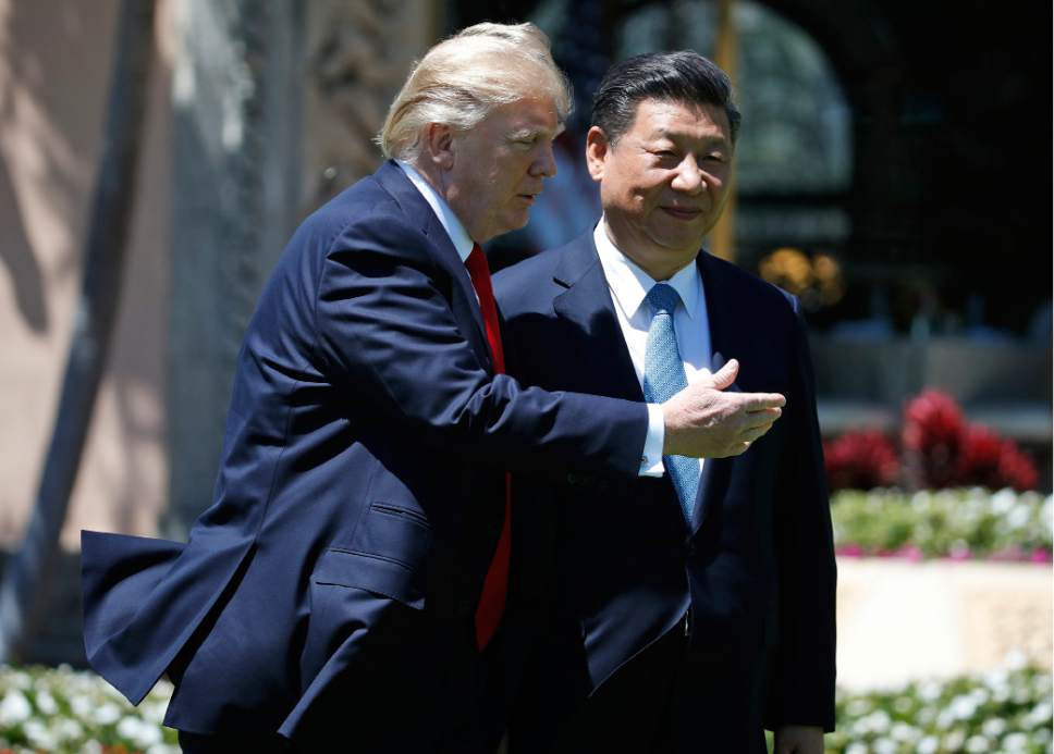 President Donald Trump gestures as he and Chinese President Xi Jinping walk together after their meetings at Mar-a-Lago, Friday, April 7, 2017, in Palm Beach, Fla. Trump was meeting again with his Chinese counterpart Friday, with U.S. missile strikes on Syria adding weight to his threat to act unilaterally against the nuclear weapons program of China's ally, North Korea. (AP Photo/Alex Brandon)
