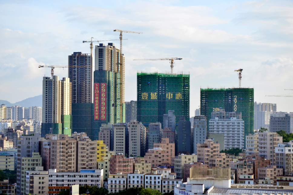 --FILE--New high-rise residential apartment buildings are under construction among others in Shenzhen city, south China's Guangdong province, 26 May 2016.  Surging property prices in Shenzhen, China's technology hub, will restrict the city's development in the long term, analysts say. In the first quarter of 2016, Shenzhen's economic growth came in at 8.4 per cent, outpacing that of Beijing and Shanghai, but its home prices are growing at an even faster rate. A number of companies, including telecommunications giant Huawei Technologies, are reportedly considering moving out of Shenzhen because of surging costs. ZTE, another telecommunications gear maker, plans to move its phone production and assembly business to Heyuan in north Guangdong by July. Although Huawei denied the news about moving, chairman Ren Zhengfei acknowledged the cost pressure the company has faced and said expensive property prices could destroy Shenzhen's competitiveness.