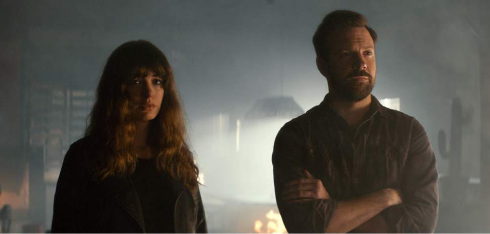 """In this image released by Neon, Jason Sudeikis, right, and Anne Hathaway appear in a scene from, """"Colossal."""" (Neon via AP)"""