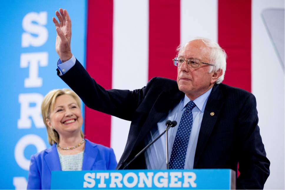 Democratic presidential candidate Sen. Bernie Sanders, I-Vt., right, accompanied by Democratic presidential candidate Hillary Clinton, left, endorses Clinton at a rally at Portsmouth High School in Portsmouth, N.H., Tuesday, July 12, 2016. (AP Photo/Andrew Harnik)