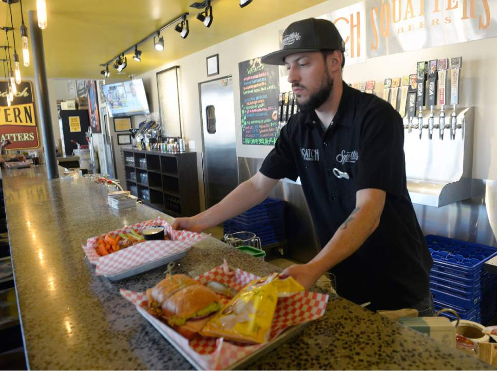 Al Hartmann  |  The Salt Lake Tribune Bartender Matt Green serves up a turkey guac sandwich and order of Squatters Legendary Buffalo Wings at West Side Tavern, a new bar that has opened as part of the Wasatch/Squatters Beer Store at 1763 W. 300 South in Salt Lake City.