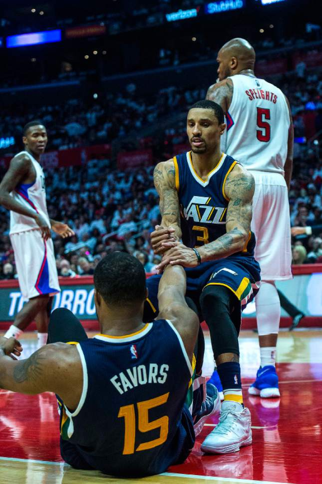 Chris Detrick     The Salt Lake Tribune Utah Jazz guard George Hill (3) helps up Utah Jazz forward Derrick Favors (15) during Game 1 of the Western Conference at the Staples Center Saturday, April 15, 2017.  Utah Jazz defeated LA Clippers 97-95.