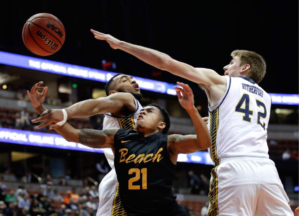 Long Beach State's Justin Bibbins, center, is defended by UC Irvine's Tommy Rutherford, right, and Jonathan Galloway during the first half of an NCAA college basketball game at the Big West men's tournament Friday, March 10, 2017, in Anaheim, Calif. (AP Photo/Jae C. Hong)