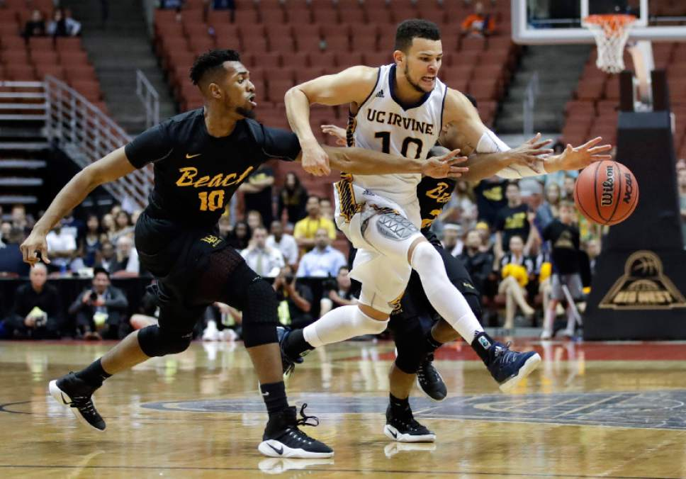 UC Irvine's Luke Nelson, center, is defended by Long Beach State's Quentin Shropshire, left, and Justin Bibbins during the second half of an NCAA college basketball game at the Big West men's tournament Friday, March 10, 2017, in Anaheim, Calif. UC Irvine won 62-57. (AP Photo/Jae C. Hong)
