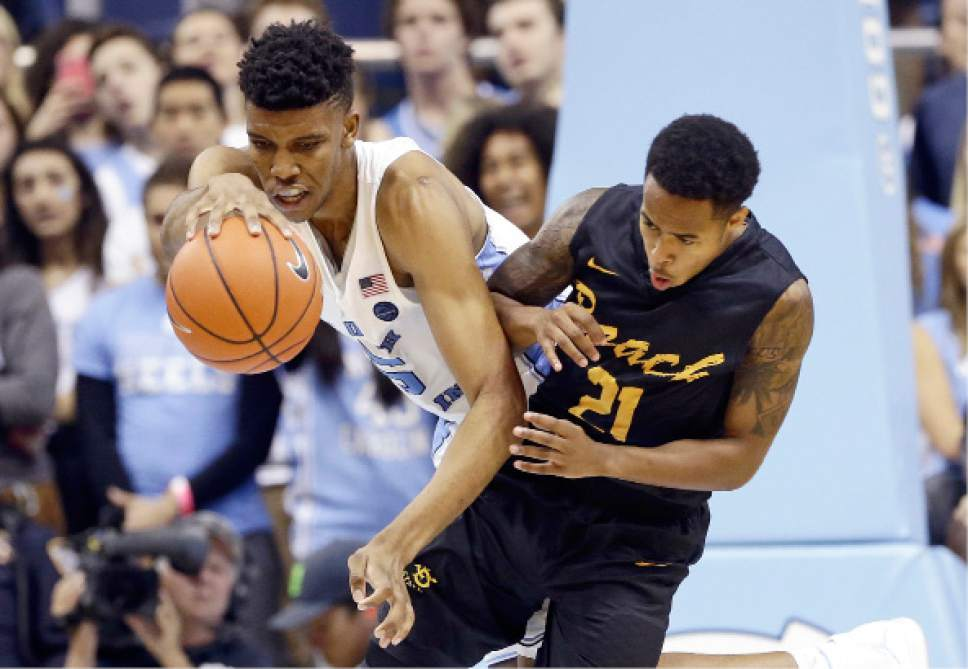 North Carolina's Tony Bradley, left, and Long Beach State's Justin Bibbins (21) chase the ball during the second half of an NCAA college basketball game in Chapel Hill, N.C., Tuesday, Nov. 15, 2016. North Carolina won 93-67. (AP Photo/Gerry Broome)