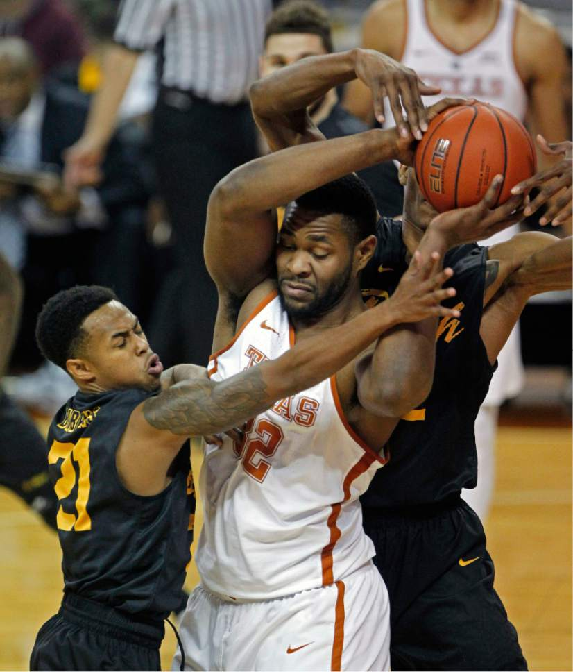 Texas forward Shaquille Cleare, center, fights for the ball with Long Beach State's Justin Bibbins, left, and LaRond Williams, right, during the first half of an NCAA college basketball game, Saturday, Dec. 10, 2016, in Austin, Texas. (AP Photo/Michael Thomas)