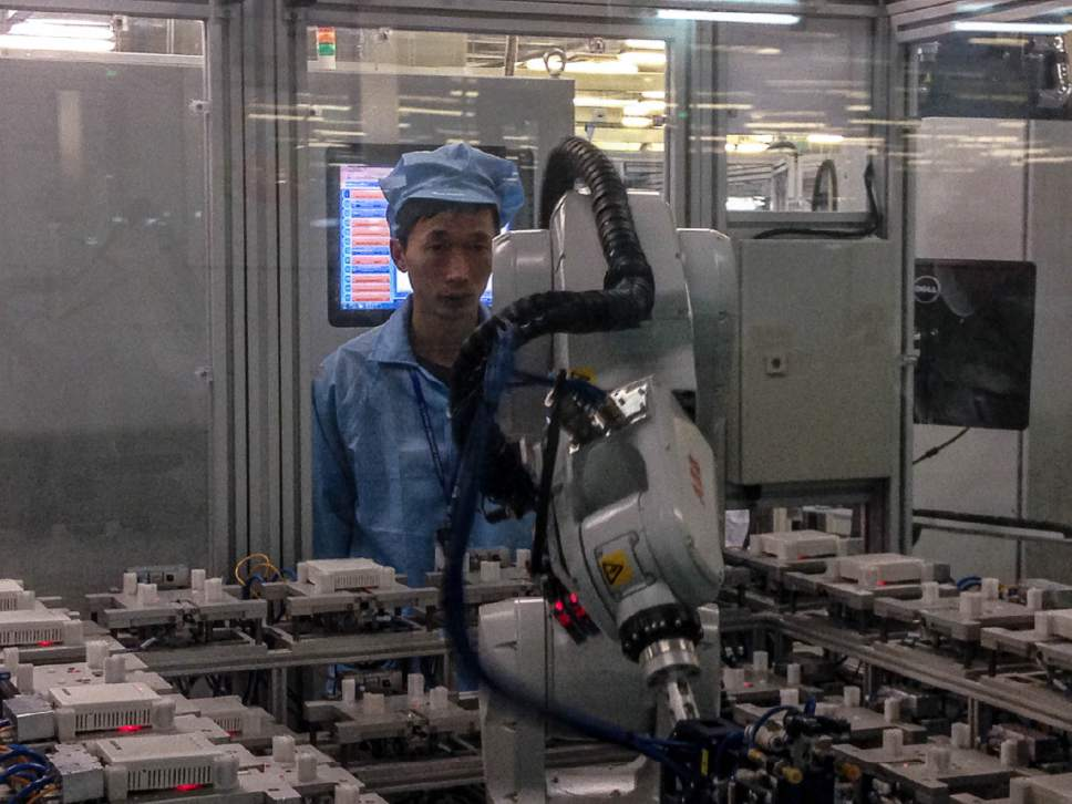 Tony Semerad | The Salt Lake Tribune Human factory workers at Shanghai-based Cambridge Industries, or CIG, operate alongside an increasing number of robots as CIG moves aggressively to automate its production of routers, smart-home devices and cel phone components. Despite having 1.357 billion people, Çhina is struggling with a worker shortage, stemming in large part from its decades-long One Child populaton controls.