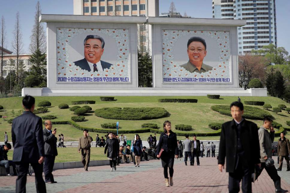 North Koreans walk along downtown Pyongyang where portraits of the late leaders, Kim Il Sung, left, and Kim Jong Un, are seen in the background Tuesday, April 18, 2017, in North Korea. Tensions have spiked in recent weeks over North Korea's advancing nuclear technology and missile arsenal. But in Pyongyang, where war would mean untold horrors, where neighborhoods could be reduced to rubble and tens of thousands of civilians could be killed, few people seem to care much at all. (AP Photo/Wong Maye-E)