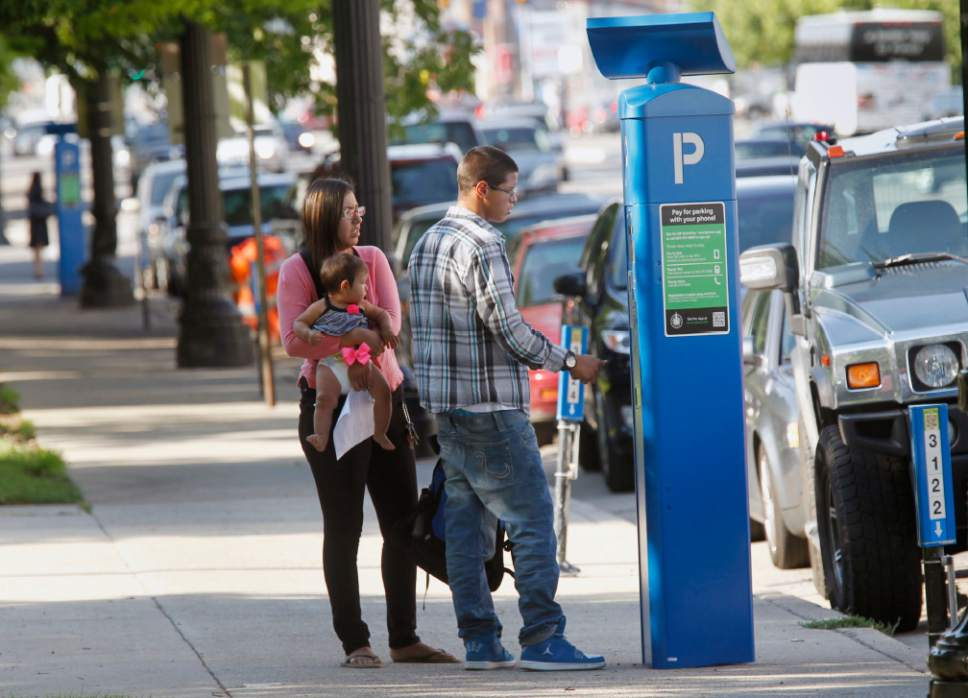 "Al Hartmann  |  The Salt Lake Tribune  Couple tries to pay for parking at pay station on State Street in Salt Lake City Tuesday July 9, 2013 despite the message that says ""free parking.""  The machines can be confusing to new users."