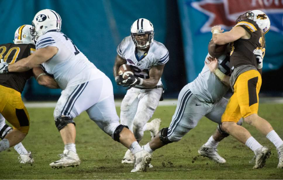 Rick Egan  |  The Salt Lake Tribune  Brigham Young offensive lineman Tuni Kanuch (78) and offensive lineman Tejan Koroma (56) open up a hole for running back Jamaal Williams (21) to run for a 36-yard touchdown for the Cougars, in the Poinsettia Bowl, at Qualcomm Stadium in San Diego, December 21, 2016.