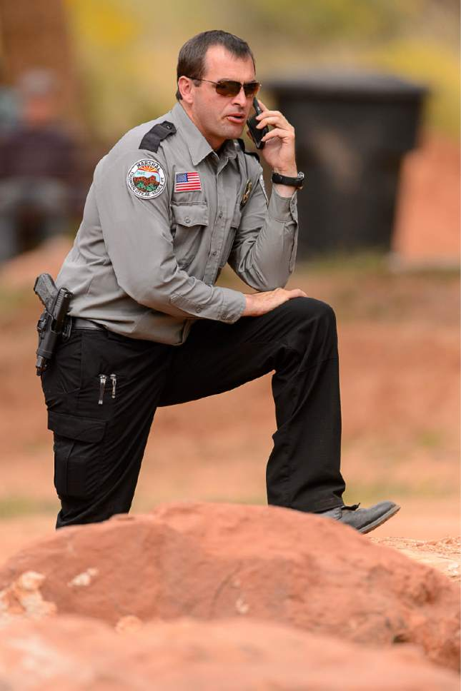 Trent Nelson  |  The Salt Lake Tribune A Colorado City/Hildale Marshal Jerry Darger on the phone at a memorial for the 13 (and 1 still missing) victims of a September 14th flash flood. The memorial was held in Maxwell Park in Hildale, Saturday September 26, 2015.