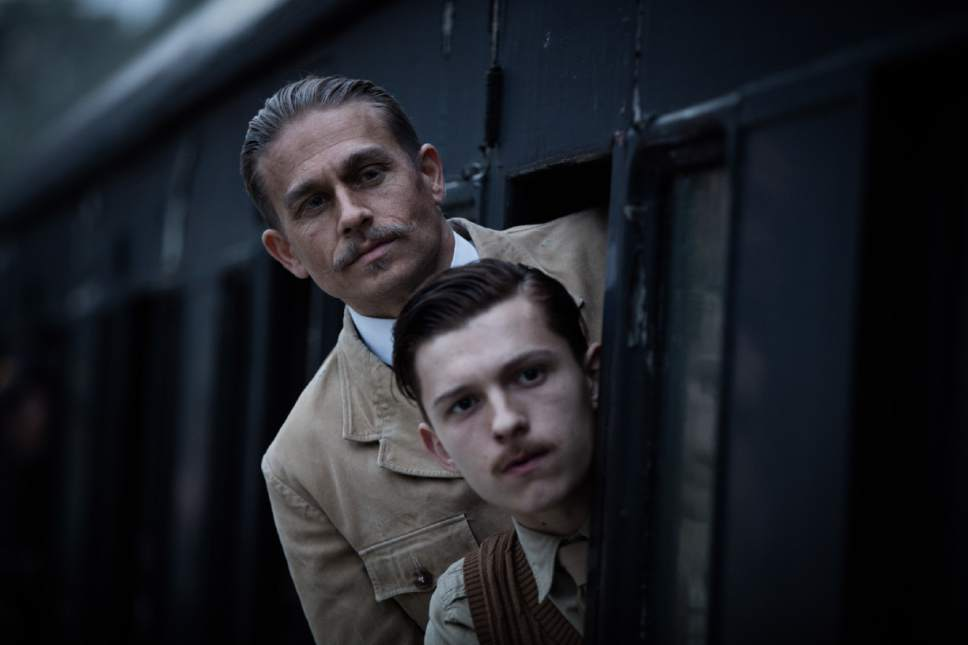 """This image released by Amazon Studios/Bleecker Street Films shows Tom Holland, foreground, and Charlie Hunnam in a scene from """"The Lost City of Z."""" (Aidan Monaghan/Amazon Studios/Bleecker Street via AP)"""