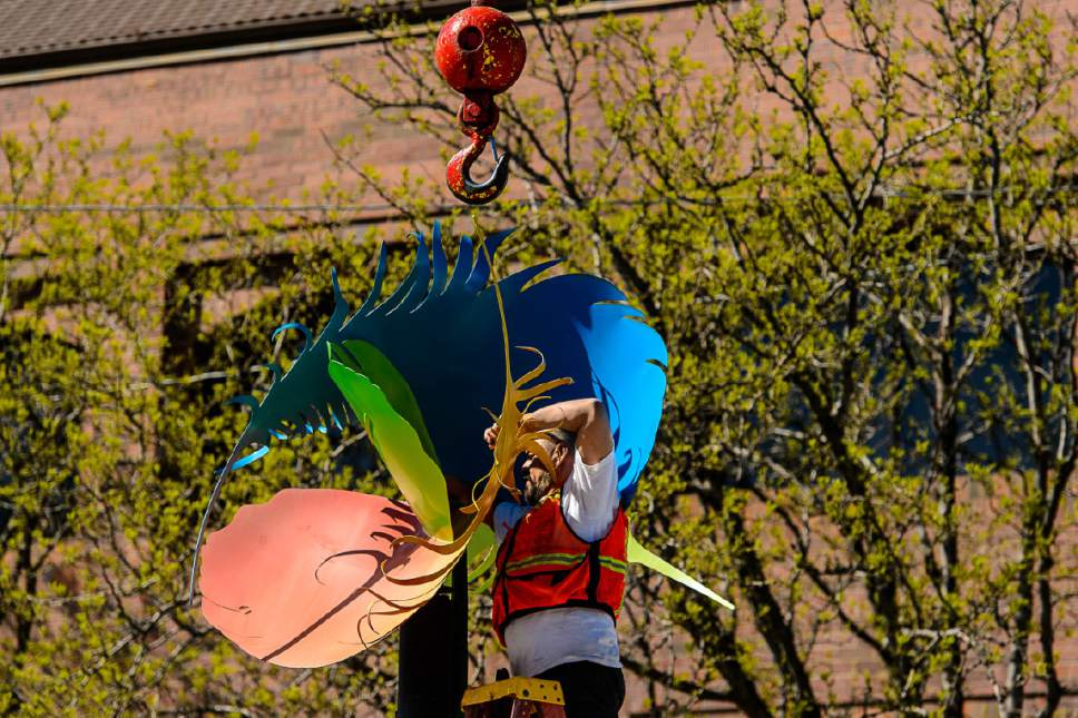"""Trent Nelson     The Salt Lake Tribune Willie Gomez works to remove Greg Ragland's piece """"Feathers in the Wind"""" from its perch along 300 South in Salt Lake City, Saturday April 15, 2017. The Salt Lake City Public Art Program spent the day installing the permanent Flying Objects public art sculpture series. The temporary series of Flying Objects, now removed, was installed in 2014 and the sculptures are currently for sale through the artists."""
