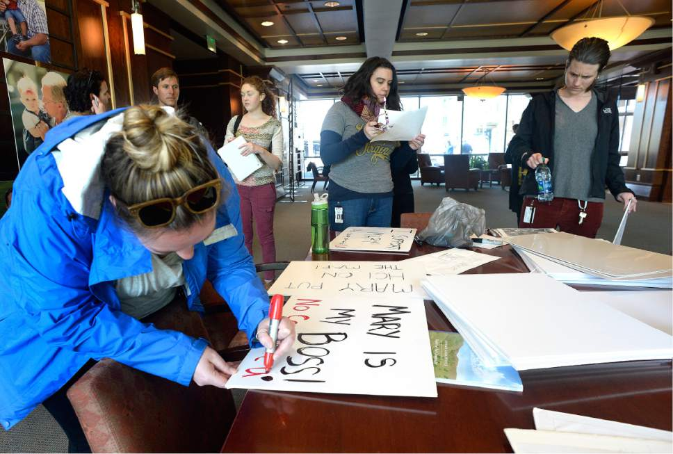 Scott Sommerdorf | The Salt Lake Tribune Danielle Hedeen, left, makes her sign along with other Huntsman Cancer Institute faculty prior to their protest march from the HCI to President's Circle to deliver their petition to Vivian Lee's office, Wednesday, April 19, 2017.