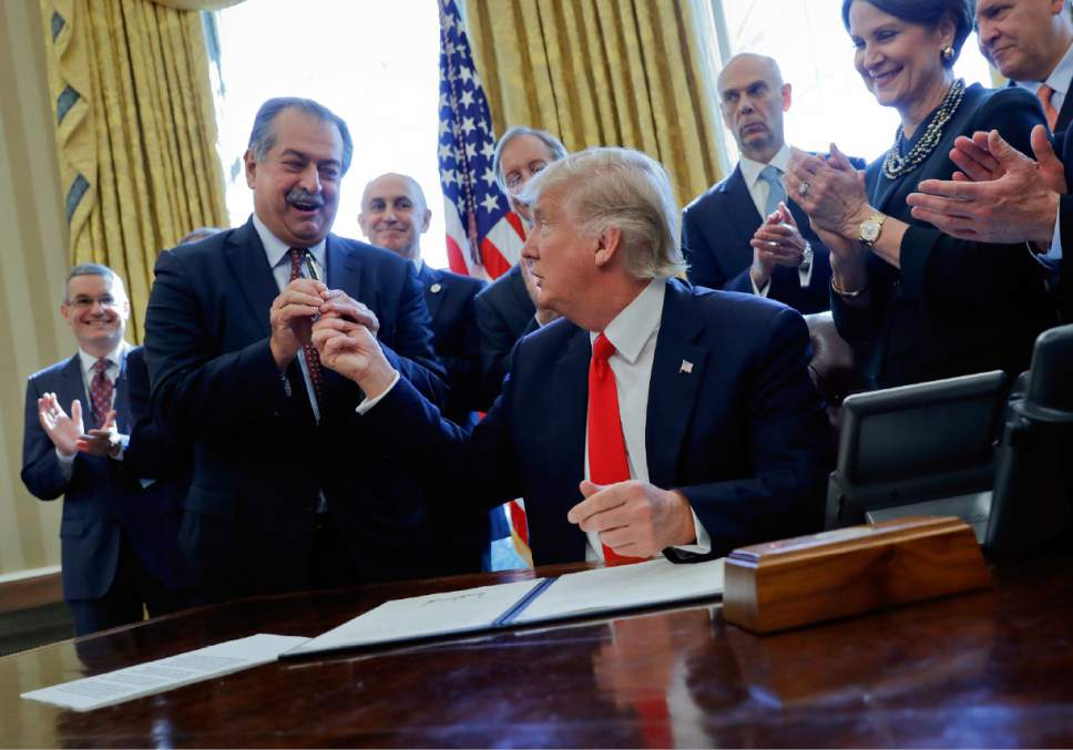 FILE - In this Feb. 24, 2017, file photo, President Donald Trump gives the pen he used to sign an executive order to Dow Chemical President, Chairman and CEO Andrew Liveris, as other business leaders applaud in the Oval Office of the White House in Washington. Dow Chemical is pushing the Trump administration to scrap the findings of federal scientists who point to a family of widely used pesticides as harmful to about 1,800 critically threatened or endangered species. Liveris is a close adviser to President Donald Trump. The company gave $1 million for Trump's inaugural activities.(AP Photo/Pablo Martinez Monsivais, File)