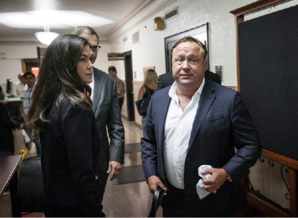 "In this Monday, April 17, 2017 photo, ""Infowars"" host Alex Jones, right, arrives at the Travis County Courthouse in Austin, Texas. Jones, the right-wing radio host and conspiracy theorist, is a performance artist whose true personality is nothing like his on-air persona, according to a lawyer defending the ""Infowars"" broadcaster in a child custody battle. (Tamir Kalifa/Austin American-Statesman via AP)"
