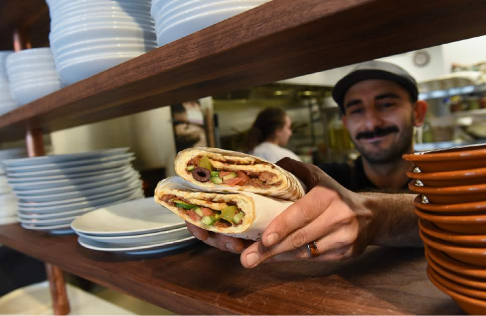 Francisco Kjolseth | The Salt Lake Tribune Moudi Sbeity, chef and owner of Laziz Kitchen, serves up Middle Eastern beef manoush wrap during a recent lunch rush at his new restaurant, in Salt Lake City's Central Ninth District.