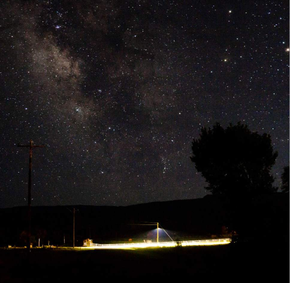 (Scott T. Smith  |  Courtesy)  The Milky Way and stars are visible in the sky above Highway 24 (Main Street) in Torrey, illuminated by a dark-sky friendly LED light.