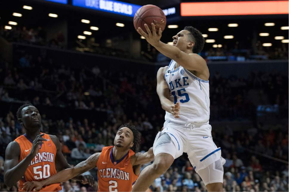 Duke guard Frank Jackson (15) goes to the basket past Clemson center Sidy Djitte (50) and guard Marcquise Reed (2) during the second half of an NCAA college basketball game in the Atlantic Coast Conference tournament, Wednesday, March 8, 2017, in New York. Duke won 79-72. (AP Photo/Mary Altaffer)