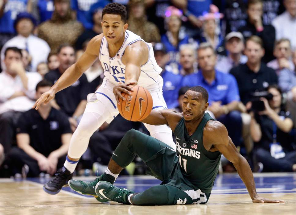 Duke's Frank Jackson and Michigan State's Lourawls Nairn Jr. (11) reach for the ball during the first half of an NCAA college basketball game in Durham, N.C., Tuesday, Nov. 29, 2016. (AP Photo/Gerry Broome)