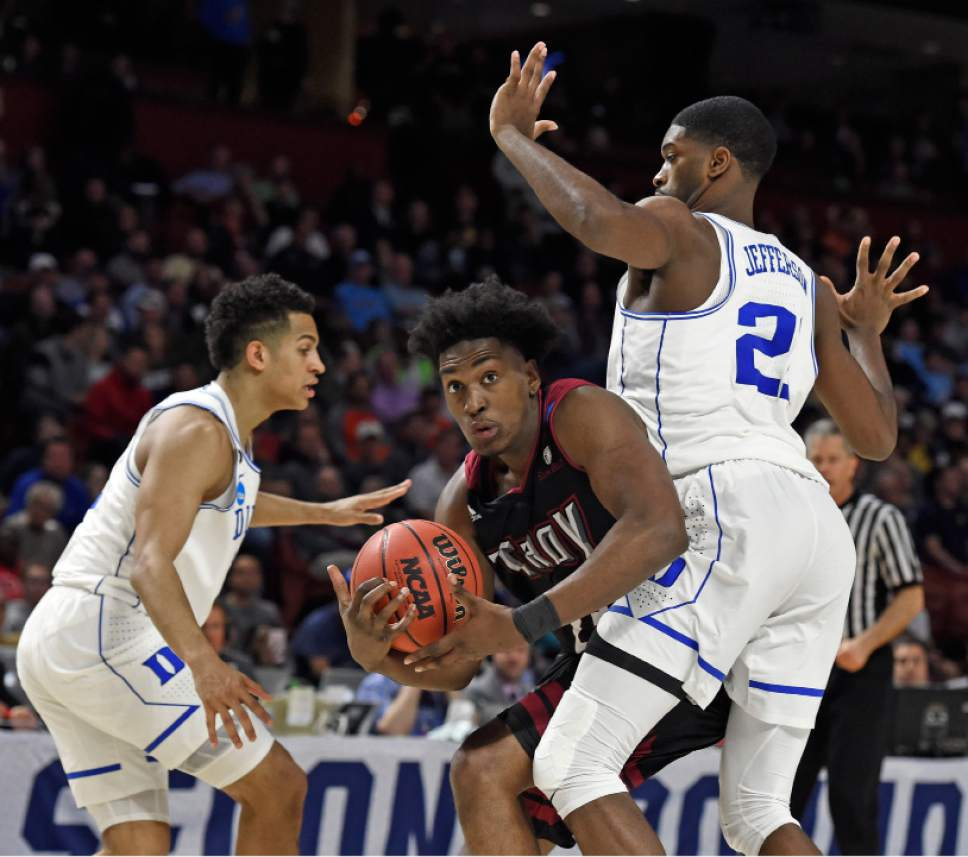 Troy's Jordon Varnado, center, drives around Duke's Chase Jeter, right, and Frank Jackson, left, during the second half in a first-round game of the NCAA men's college basketball tournament in Greenville, S.C., Friday, March 17, 2017. (AP Photo/Rainier Ehrhardt)