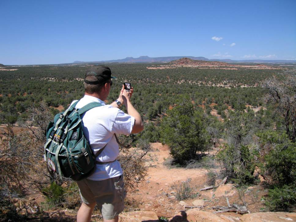 Al Hartmann  |  The Salt Lake Tribune  Hiker takes a compass bearing before walking across part of Cedar Mesa in San Juan County.  Prominent Bears Ears formation visible in the distance. The area is included for a proposed Bears Ears National Monument.