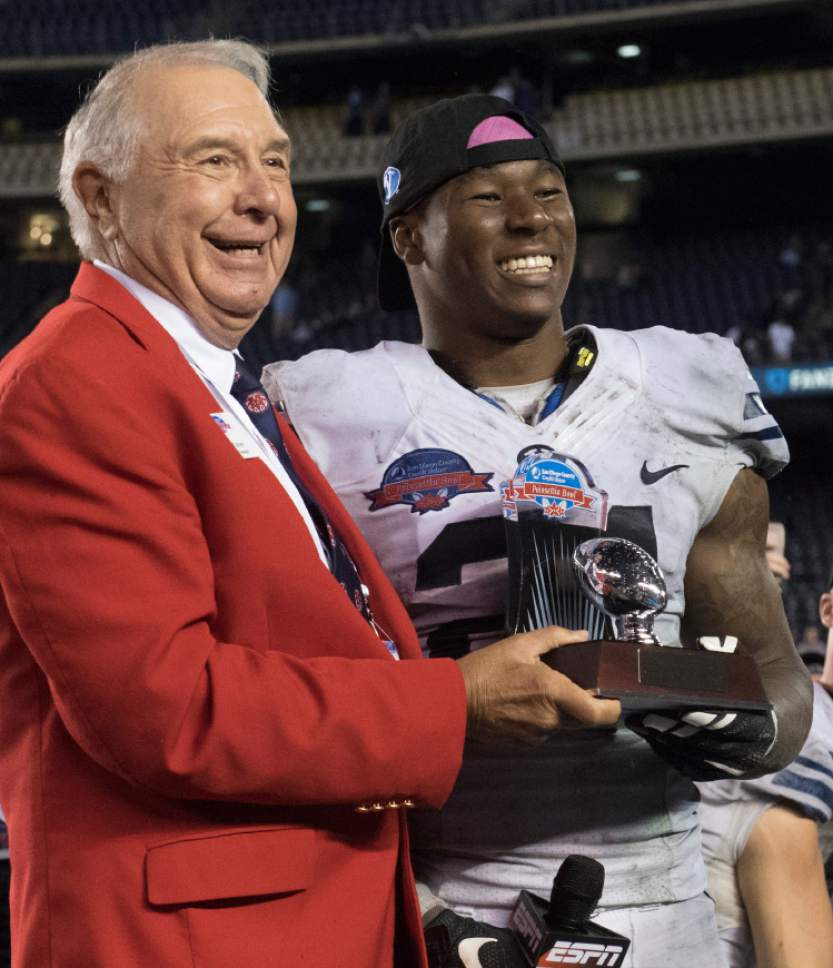Rick Egan  |  The Salt Lake Tribune  Ted Tollner, Poinsettia Bowl President, presents  Brigham Young Cougars running back Jamaal Williams (21) the trophy for offensive MVP, in the Poinsettia Bowl, at Qualcomm Stadium in San Diego, December 21, 2016.