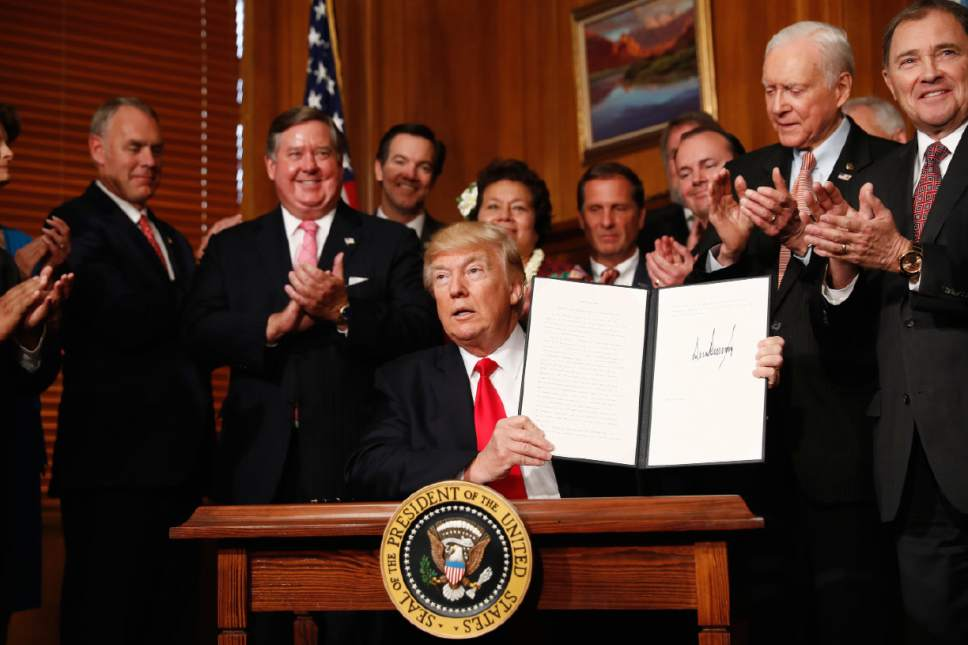 """President Donald Trump holds up a signed Antiquities Executive Order during a ceremony at the Interior Department in Washington, Wednesday, April, 26, 2017. The president is asking for a review of the designation of tens of millions of acres of land as """"national monuments."""" (AP Photo/Carolyn Kaster)"""