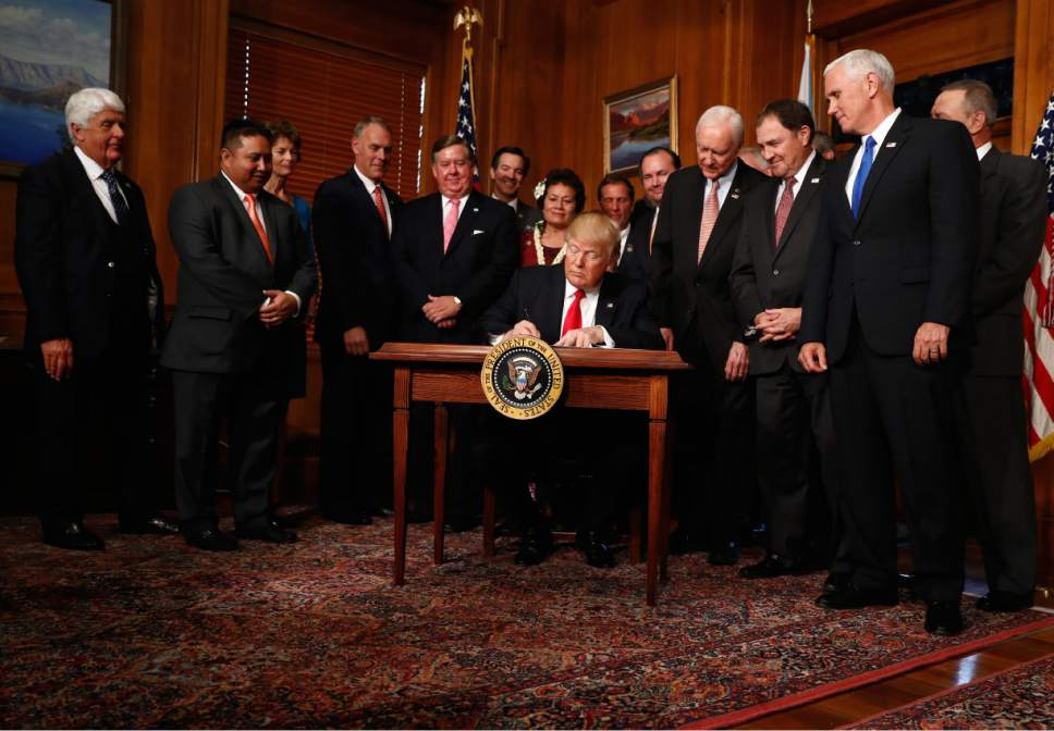 """President Donald Trump signs an Antiquities Executive Order during a ceremony at the Interior Department in Washington, Wednesday, April, 26, 2017. President Donald Trump is asking for a review of the designation of tens of millions of acres of land as """"national monuments."""" (AP Photo/Carolyn Kaster)"""