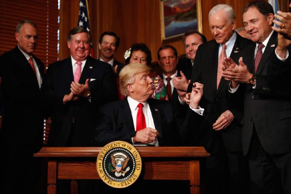 """President Donald Trump hands a pen to Sen. Orrin Hatch, R-Utah after signing an Antiquities Executive Order during a ceremony at the Interior Department in Washington, Wednesday, April, 26, 2017. The president is asking for a review of the designation of tens of millions of acres of land as """"national monuments."""" (AP Photo/Carolyn Kaster)"""